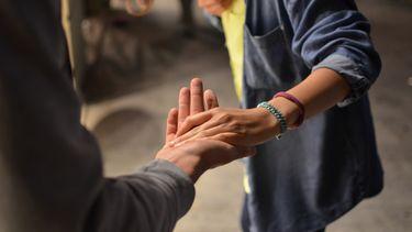 twee mensen houden elkaars hand vast tijdens een eerste indruk