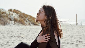 Vrouw op strand met ogen dicht , waarbij mythen rondom gezondheid wordt ontkracht