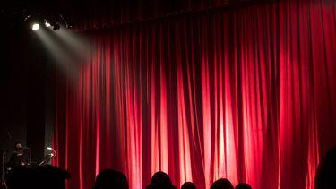 Mensen in een theaterzaal, die niet naar een online theatervoorstelling voor kinderen kijken