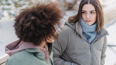 twee vriendinnen staan buiten en een vriendin kijkt jaloers naar de ander