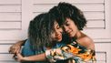 Twee vrouwen die elkaar knuffelen en jeugdvrienden zijn
