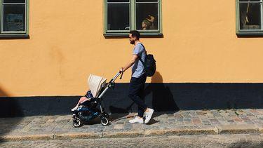 Man die op straat een kinderwagen duwt