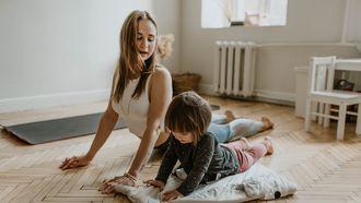Moeder en kind die samen yoga aan het doen zijn