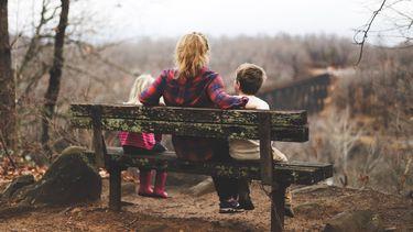 een hoogsensitieve ouder en kinderne op een bankje in de natuur