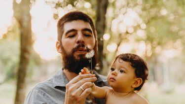 Man draagt zijn baby en blaast op bloem, hij is een van de type vaders