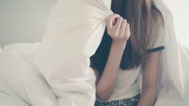 Tiener meisje dat in bed zit met de deken om haar heen