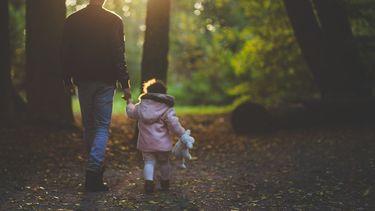 Vader en dochter die hand in hand door het bos lopen
