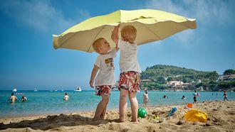 kinderen onder een paraplu in de zon