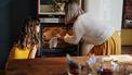 Moeder en dochter die iets uit de oven halen na het bakken voor de Sint