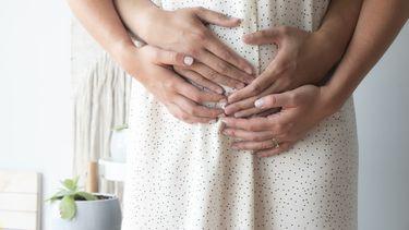 Vrouw die haar handen en de handen van haar partner op haar buik heeft omdat ze tijdens de zwangerschap toch een missed abortion heeft