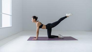 Pilates oefeningen / vrouw doet oefeningen op matje