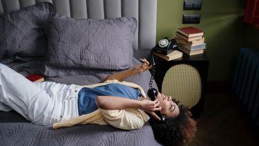 Vrouw die op bed ligt en telefoonseks heeft