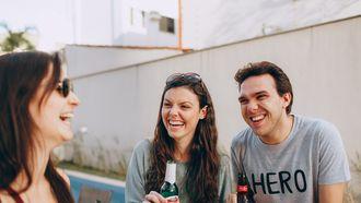 Man en vrouw lachen met een drankje in hun hand om een andere vrouw. Makkelijk psychologische trucjes toepassen zodat de ander je leuk gaat vinden