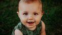 Een baby die in de camera kijkt en lacht met een Portugese babynaam