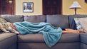 vrouw die misselijk op de bank ligt onder een deken