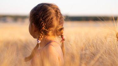 klein meisje staat in een veld
