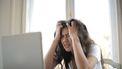Vrouw zit met handen in het haar gefrustreerd voor haar laptop (en kan tips voor stressbestendigheid goed gebruiken)