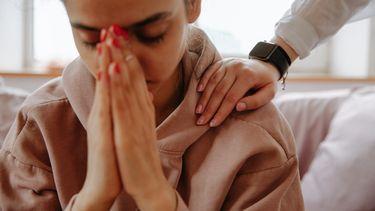 Vrouw zit verdrietig met handen voor haar gezicht, mogelijk een zomerdepressie