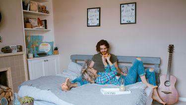 Stelletje dat samen op bed ligt en pizza eet