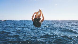 man maakt een bommetje in het water in de zomer