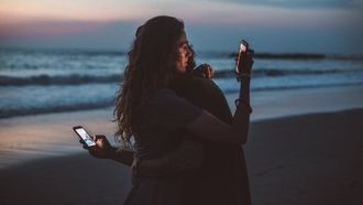 social media / stel knuffelt en kijkt op telefoon