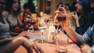 Een vriendengroep die wijn drinkt aan tafel