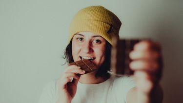Vrouw met gele muts die chocolade eet en een stukje aanbiedt aan de camera