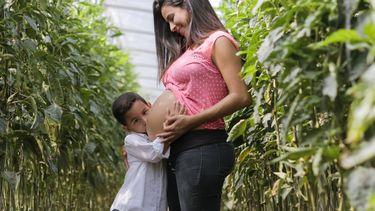 kind knuffelt de buik met de baby van de moeder