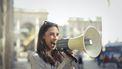 vrouw roept vrolijk in megafoon alsof ze anderen een compliment geeft