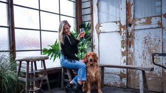 Vrouwdie wijn drinkt met haar hond