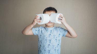 Kind dat twee wc-rollen voor zijn ogen houdt