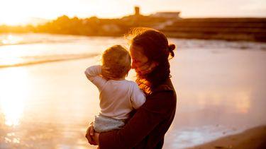 Moeder met baby op het strand en overleeft het eerste jaar met boek van franke van hoeven