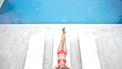 Vrouw die in haar bikini op een zonnebedje ligt en een van de schaamhaartrends heeft toegepast