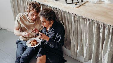 Man en vrouw die op de grond aan het emotie eten zijn