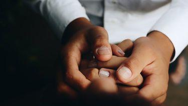 koppel houdt elkaars handen vast