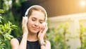 Vrouw met witte headphone lacht en luistert naar muziek, ze gebruikt muziek als therapie