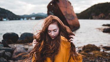 vrouw op stenen strand haalt handen door haar lange haren, alsof ze van jeukende hoofdhuid af wilt