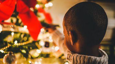 Jongetje die een bal in de kerstboom hangt