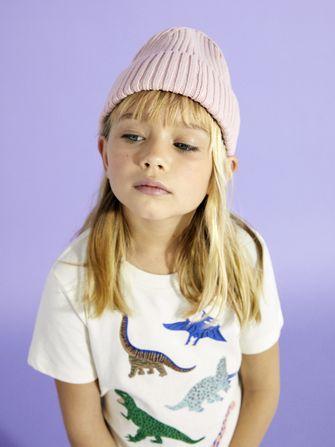 Meisje met roze muts en dino t-shirt van de zomercollectie