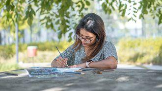 Vrouw die haar geboortekaartjes schrijft