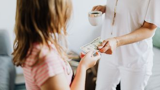 Kind dat zakgeld krijgt van haar moeder om te leren omgaan met geld