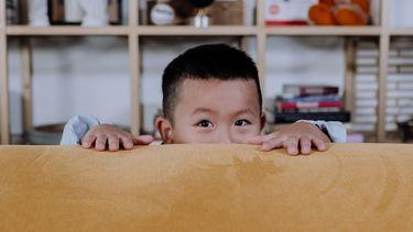Kind dat van achter de bank spiekt omdat hij iets verborgen houdt voor zijn ouders