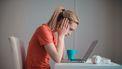 Vrouw zit met beide handen voor haar laptop; alsof zwangerschapsdementie toeslaat