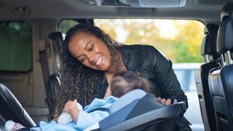 Moeder die haar baby in een autostoeltje in de auto zet