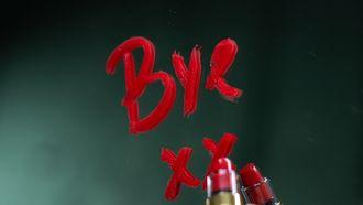 Een vrouw die gaat scheiden en met lippenstift 'Bye' schrijft op de spiegel