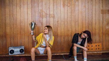 twee vrouwen op een bankje terwijl een overwinningsbeker vast heeft en de ander somber kijkt en bedenkt waarom je jezelf niet moet vergelijken met anderen