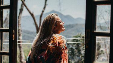 meisje kijkt uit het raam en lacht vrolijk omdat ze van zichzelf houdt