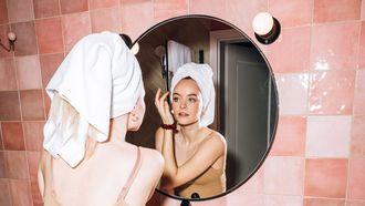 vrouw verzorgt haar huid volgens haar skincare routine in de spiegel