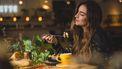 vrouw zit te eten in restaurant omdat ze cravings heeft