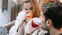 Vrouw die de man aankijkt tijdens hun date terwijl ze koffie drinkt, omdat ze benieuwd is wat de man het eerst aan haar opvalt